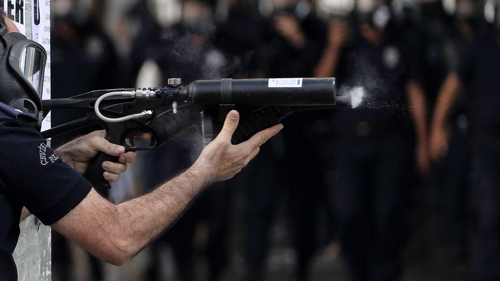 Policía apunta con un arma a los manifestantes en Ankara