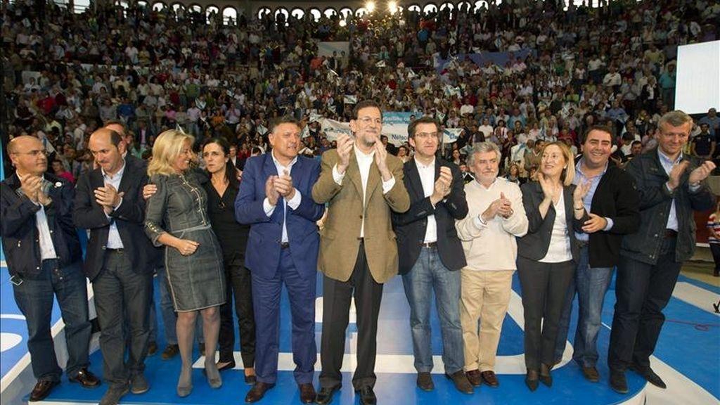El presidente del PP, Mariano Rajoy (c) posa junto al máximo responsable del partido en Galicia, Alberto Núñez Feijóo (5d), entre otros asistentes, durante el acto de la precampaña para las próximas elecciones municipales que se ha celebrado esta tarde en la plaza de toros de Pontevedra. EFE