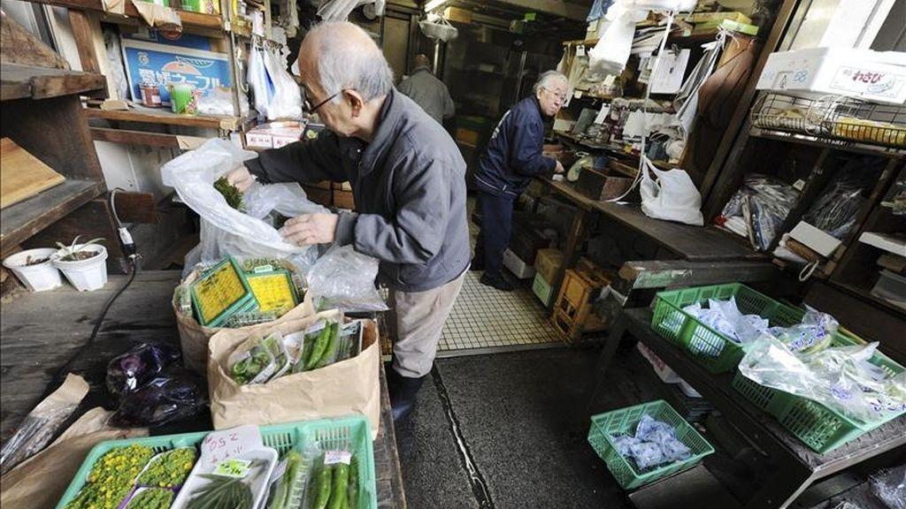Un vendedor de verduras comprueba cajas con mercancía en un puesto del mercado de Tsukiji en el centro de Tokio (Japón). EFE/Archivo