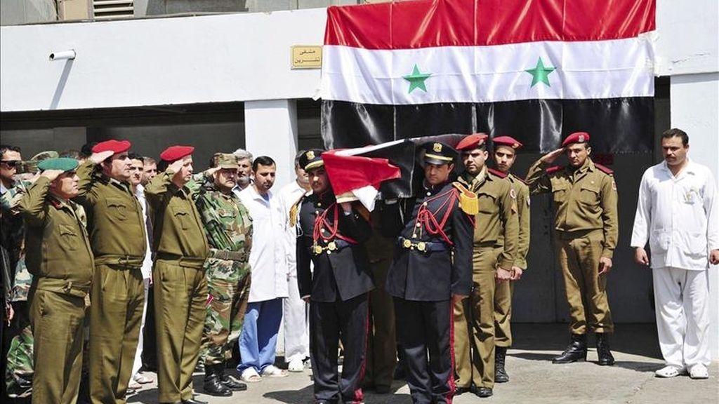 Foto facilitada por la agencia oficial siria, SANA, que muestra el traslado de los ataúdes con los restos de 15 oficiales y guardias sirios desde el hospital Tishrin de Damasco, Siria, hoy, martes 26 de abril de 2011. EFE