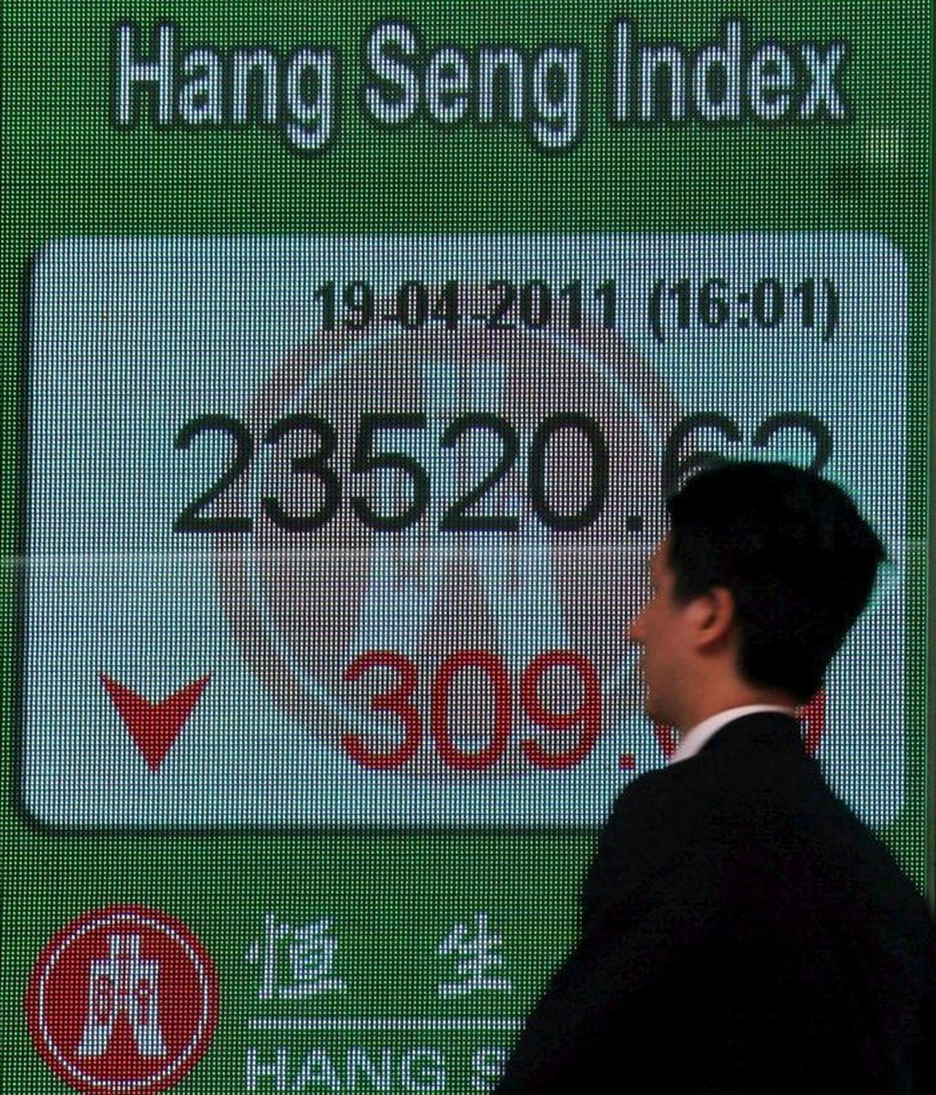 Un hombre pasa delante de un panel electrónico que muestra el valor alcanzado por el índice Hang Seng de la Bolsa de Hong Kong. EFE/Archivo