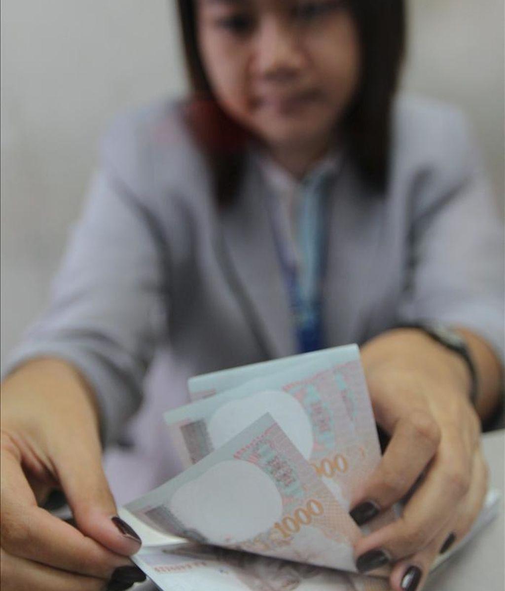 Una mujer cuenta dinero en un local de cambio de divisas en Bangkok, Tailandia. EFE/Archivo