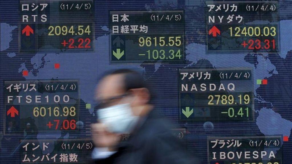 Un hombre camina frente a un tablero electrónico con los resultados de la Bolsa de Tokio. EFE/Archivo