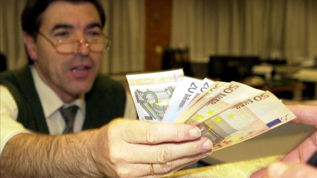 Un empleado de banca muestra los billetes de euro. EFE/Archivo
