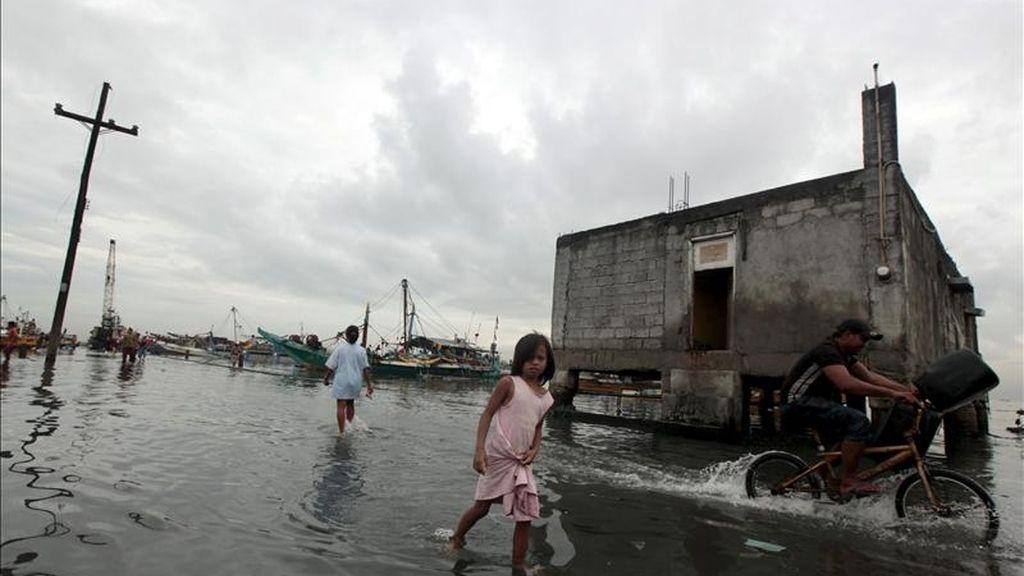Los residentes caminan en una zona inundada de su localidad tras el paso de la tormenta tropical 'Aere' en Manila, Filipinas. EFE
