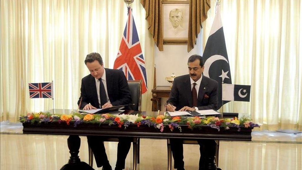 El primer ministro británico, David Cameron (izq), y su homólogo paquistaní, Yusuf Raza Gilani (dcha), firman un acuerdo sobre diálogo estratégico bilateral durante un encuentro mantenido en Islamabad (Pakistán). Cameron llegó al país para realizar una visita de un día de duración. EFE