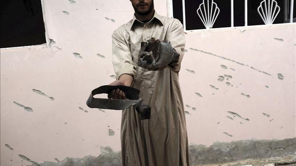 Un libio muestras las piezas de un misil disparado presuntamente por las fuerzas leales al líder libio Muamar el-Gadafi, en Adjabiya, Libia. EFE