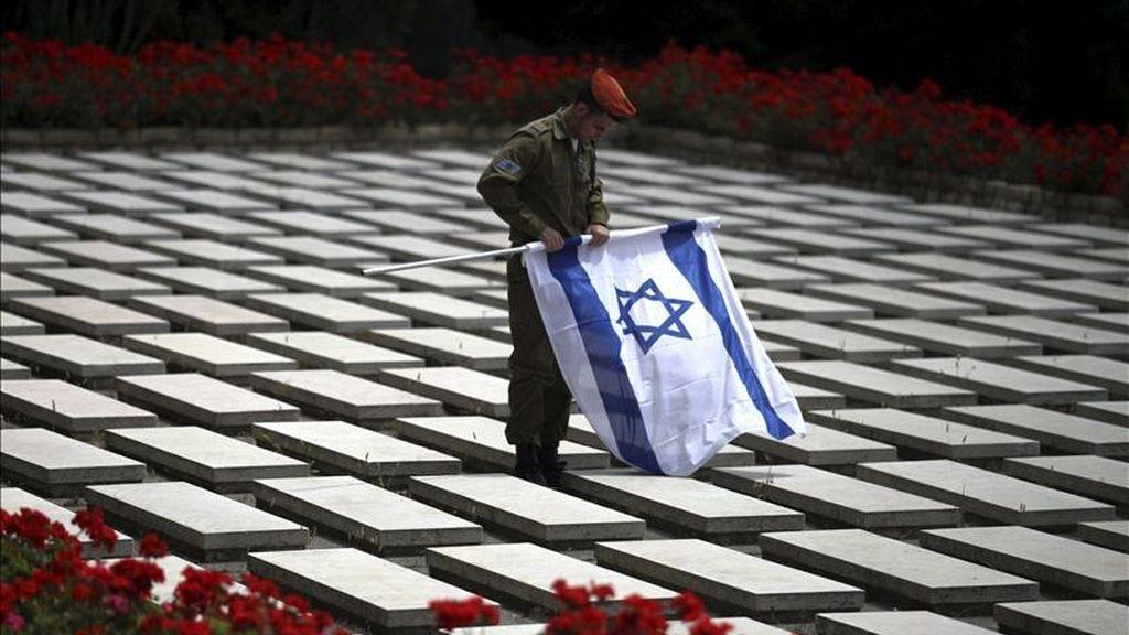 Un soldado israelí enrolla una bandera de Israel en el cementario militar del Monte Herzl, en Jerusalén, hoy, domingo, 8 de mayo de 2011. El Ejército israelí ha cerrado los accesos al territorio palestino ocupado de Cisjordania con motivo de la celebración del Día del Recuerdo y el Día de la Independencia, lo que impedirá a los palestinos acceder a territorio controlado por Israel hasta el próximo miércoles.EFE