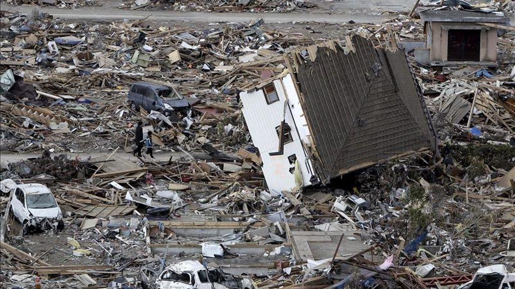 Un padre y su hijo parecen diminutos en comparación con la enormidad de los escombros que cubren por completo la devastada población costera de Ofunato, en la prefectura de Iwate, noreste de Japón. EFE