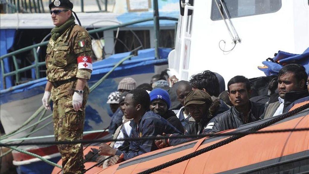 Inmigrantes subsaharianos a bordo de un bote que partió de Misurata, Libia, hace cuatro días son custodiados mientras llegan al puerto de la isla italiana de Lampedusa. EFE