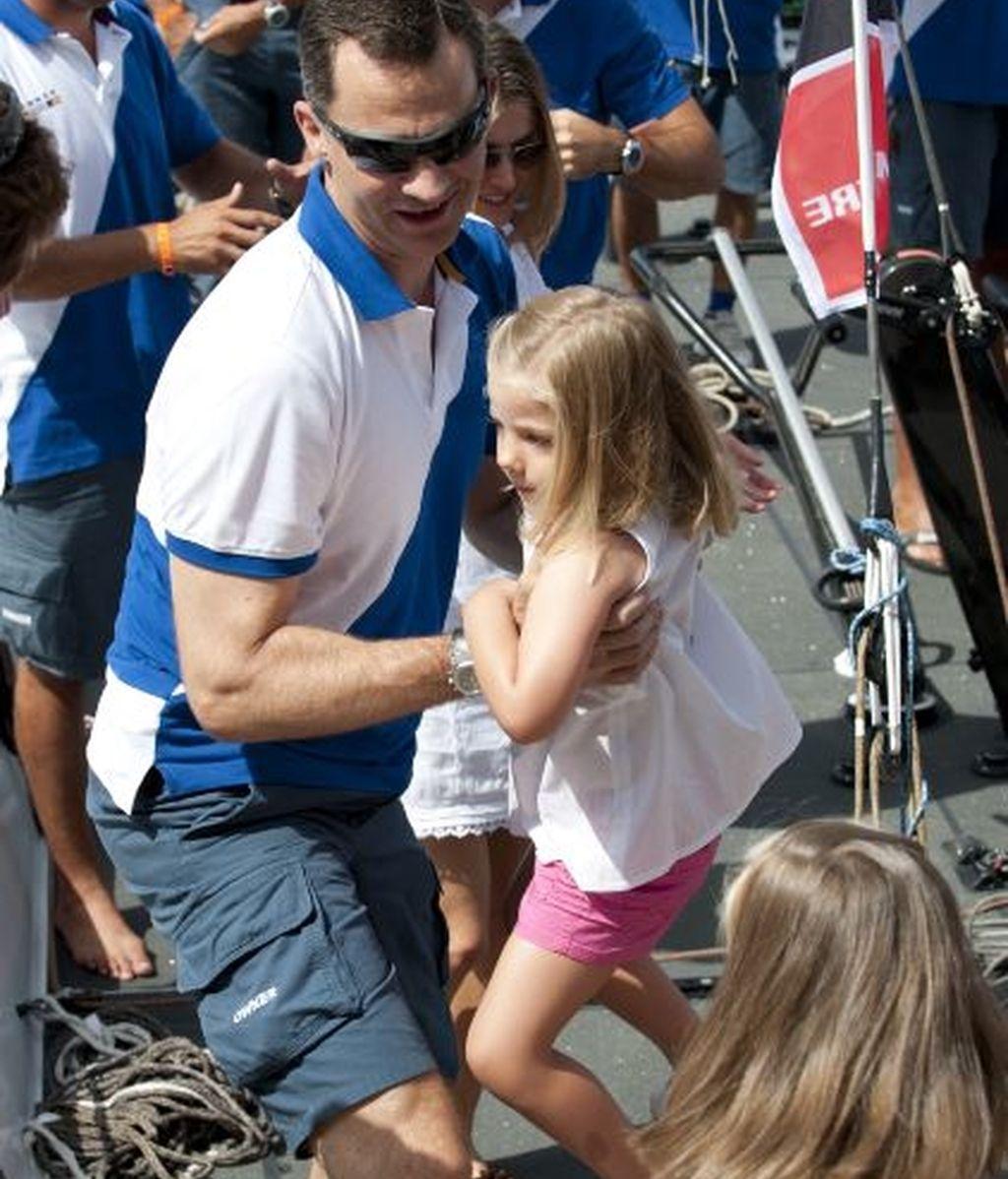 Felipe ayuda a una de sus hijas a subir al barco