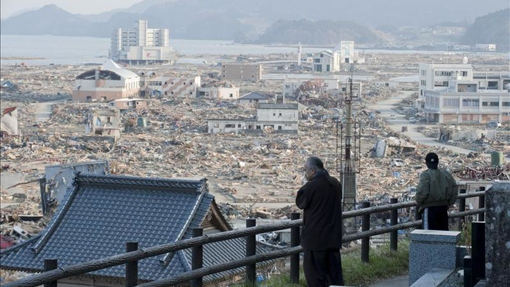 Foto facilitada ayer que muestra a dos japoneses observando el devastador paisaje que presenta la localidad de Rikuzentakada, en la prefectura de Iwate, noreste de Japón, tras el terremoto de 9 grados y tsunami del pasado 11 de marzo. EFE