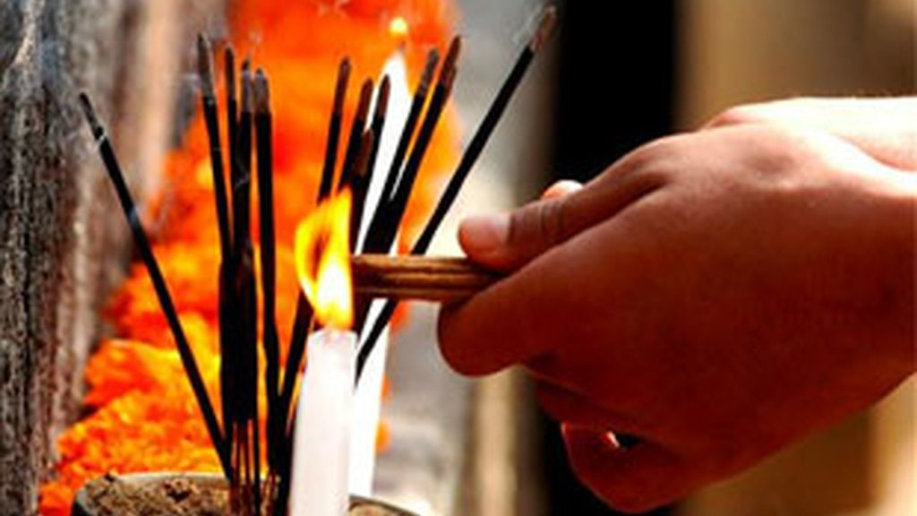 Un monje budista quema incienso. Foto: Archivo / EFE