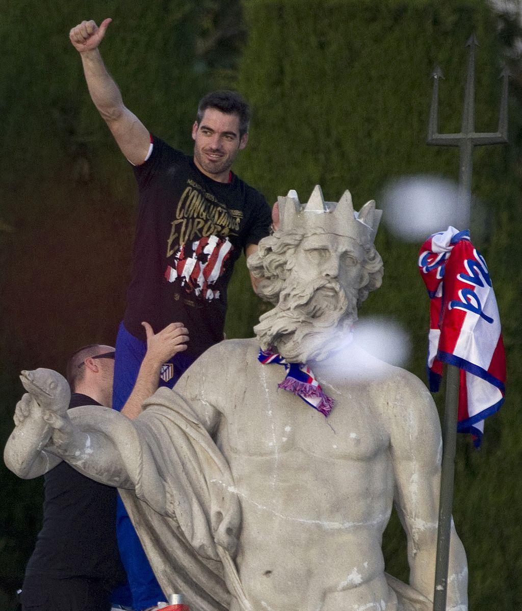 El capitán del Atlético de Madrid, Antonio López, corona la celebración del club colchonero anudando una bufanda al cuello del Dios Neptuno y una bandera en el tridente de la efigie