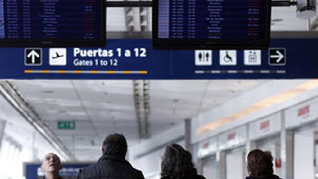 Varios pasajeros consultan las pantallas de información en el aeropuerto de Buenos Aires. Foto: Reuters