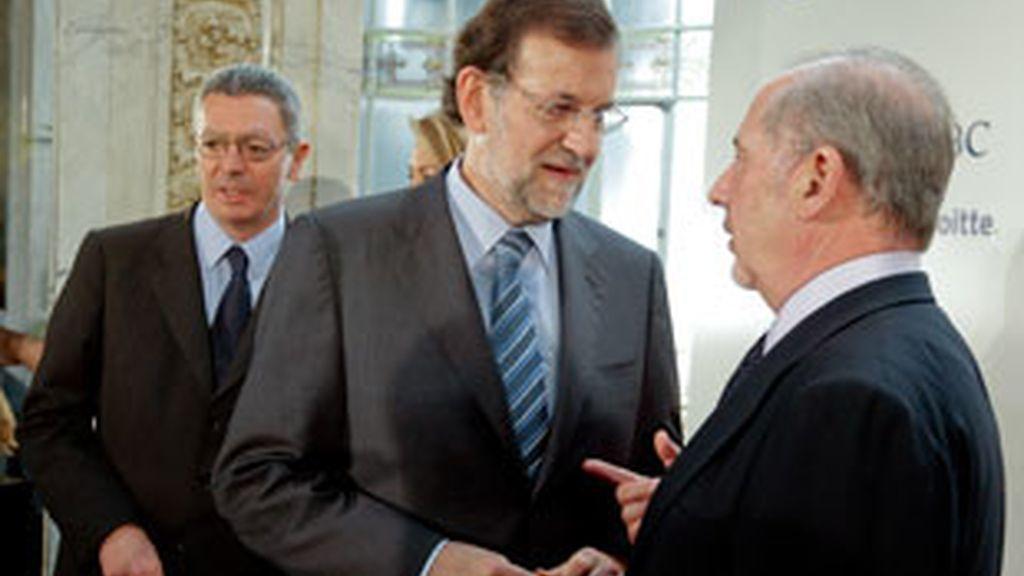 Mariano Rajoy conversa con el presidente de Bankia, Rodrigo Rato, en presencia del alcalde de Madrid. Foto: EFE.