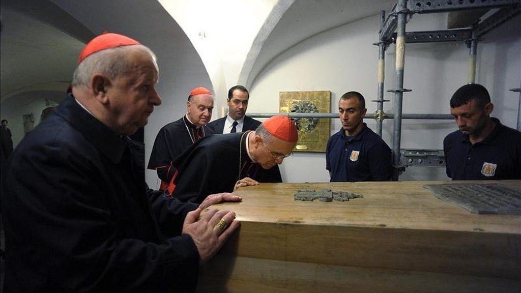 El secretario de estado del Vaticano, Tarcisio Bertone, besando el féretro del Papa Juan Pablo II. EFE/Archivo