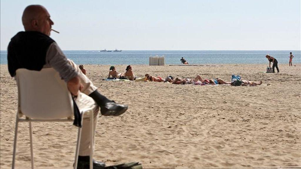 Un grupo de mujeres toma el sol este mediodía en la playa de Las Arenas de Valencia mientras un hombre fuma un cigarrillo sentado en le paseo marítimo. EFE