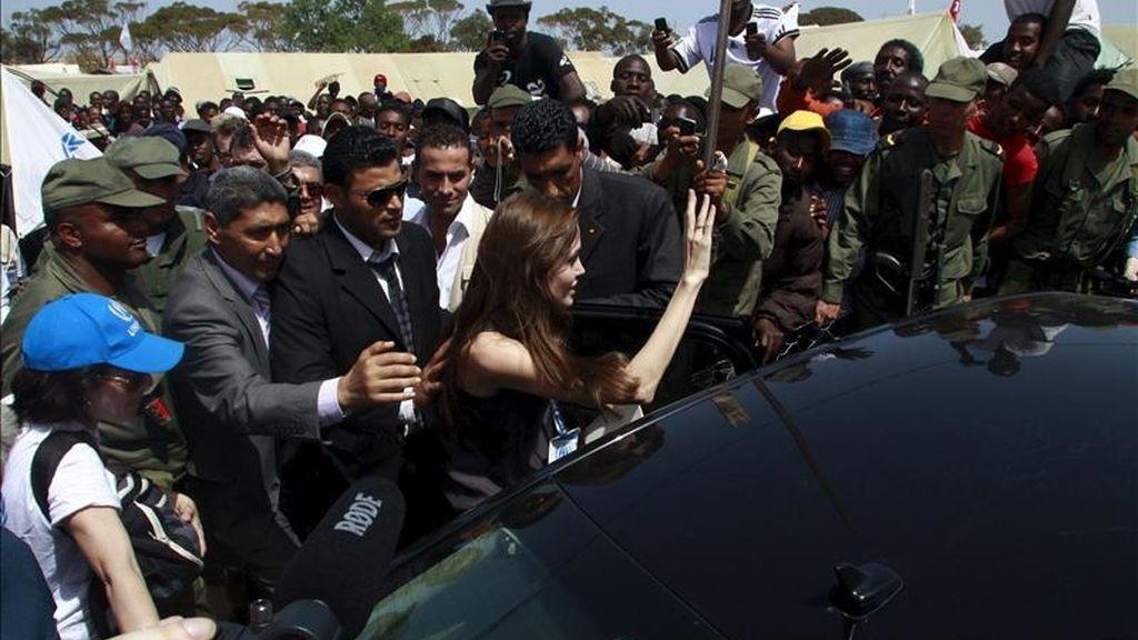 La embajadora de buena voluntad del ACNUR, la actriz estadounidense Angelina Jolie (c), saluda a los refugiados durante su visita a un campo de refugiados ubicado en la frontera entre Libia y Túnez, en Túnez. EFE