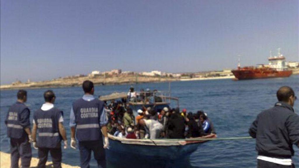 Guardacostas italianos esperan la llegada de uno de las seis embarcaciones procedentes de Libia que llegaron a Lampedusa. EFE