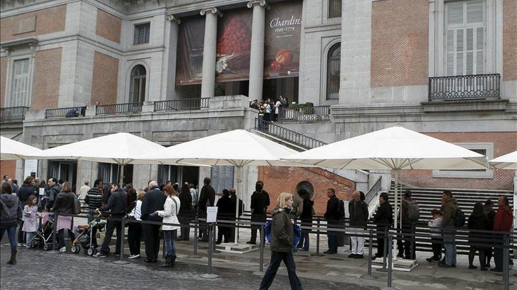 Grandes sombrillas protegen de la lluvia a una larga cola de personas que han elegido esta mañana de Jueves Santo para disfrutar de una visita al Museo del Prado. EFE