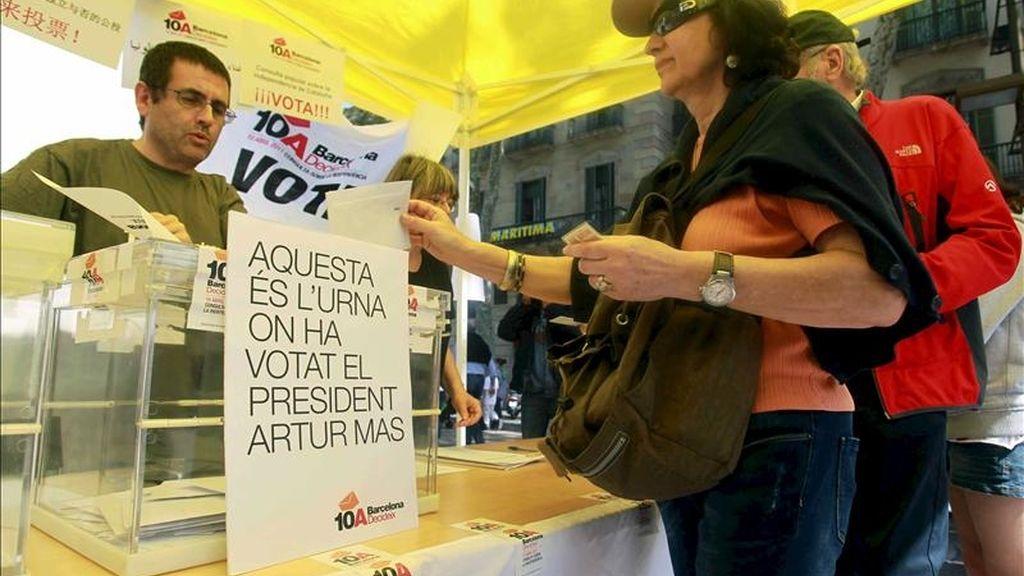 Varias personas depositan su voto en la urna en la que el presidente de la Generalitat y líder de CiU, Artur Mas, votó de forma anticipada durante la consulta sobre la independencia de Cataluña que ha organizado la plataforma Barcelona Decideix a menos de dos meses de la celebración de las elecciones municipales. EFE