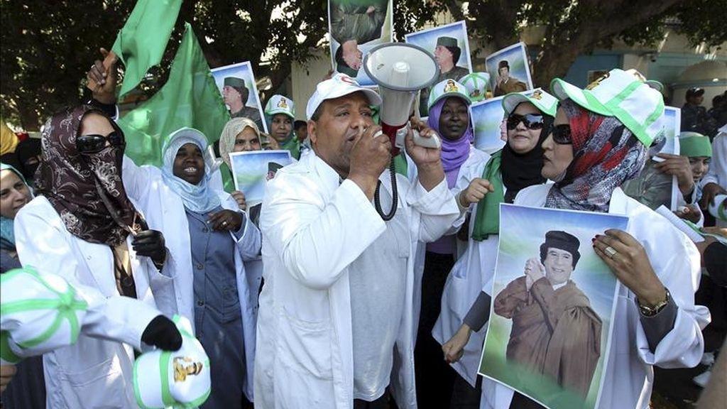 Libios leales al líder Muamar el Gadafi gritan consignas y sostienen imágenes de él durante una protesta en contra de los bombardeos aéreos de la coalición aliada sobre Libia, en las afueras de las oficinas de la ONU, en Trípoli, Libia. EFE