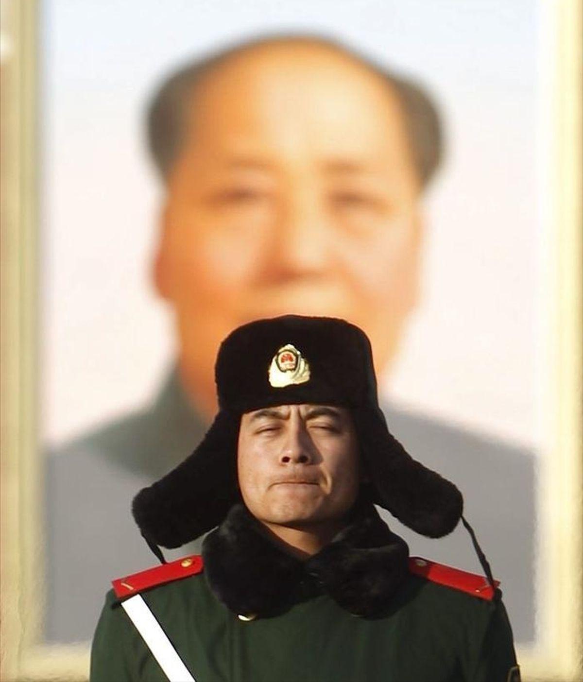 Un miembro del Ejército de Liberación del Pueblo (PLA), monta guardia delante del retrato del fundador del régimen comunista chino Mao Zedong que cuelga de la puerta de la Paz Celestial en la plaza de Tiananmen donde se ha inaugurado una estatua de Confucio. EFE/Archivo