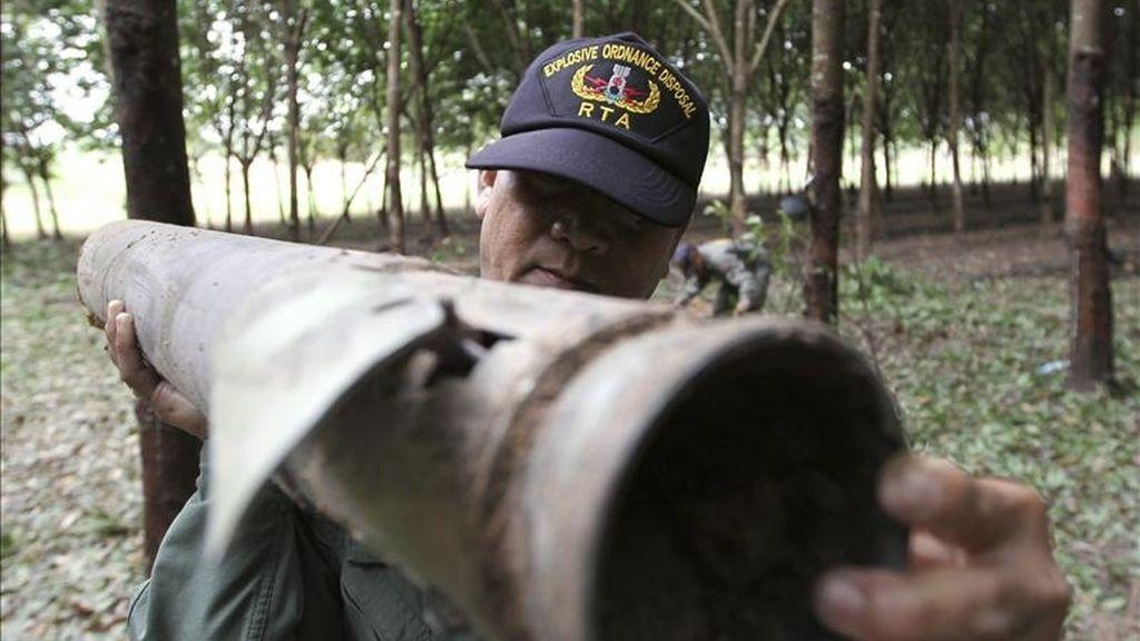 Un efectivo del cuerpo de armamento tailandés recoge parte de un proyectil lanzado por tropas camboyanos en el distrito fronterizo de Phanom Dong Rak, Tailandia. EFE/Archivo