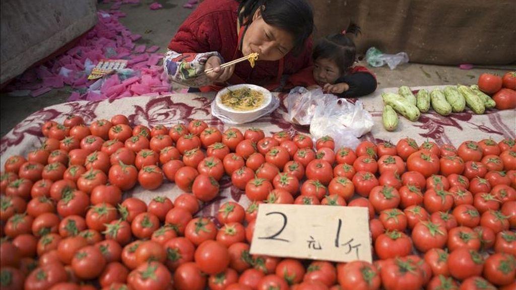 Una mujer come fideos chinos en su puesto de tomates en Qingdao (China). China registró su primer déficit comercial en seis años entre enero y marzo. EFE/Archivo