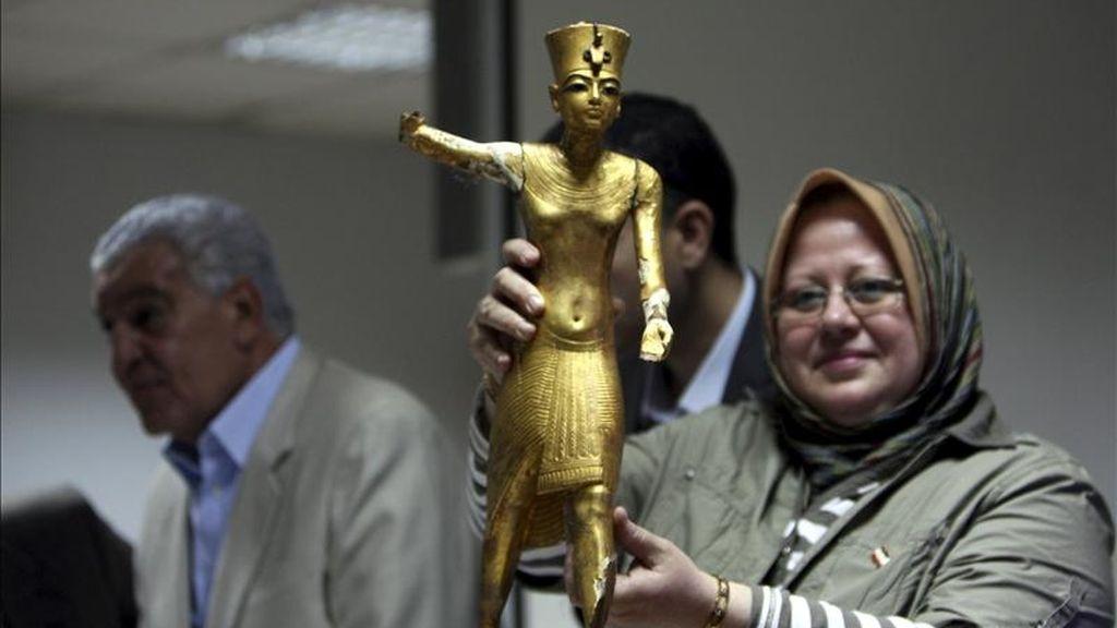 Una arqueóloga sin identificar (d) sostiene una estatua de madera dorada tras regresar al Museo Egipcio, mientras el ministro de Estado de Antigüedades, Zahi Hawas (i), conversa con los medios en El Cairo (Egipto). El arqueólogo egipcio Salah Mohamed encontró hoy por casualidad una maleta en el metro de El Cairo que contenía cuatro piezas del ajuar funerario de Tutankamón. EFE