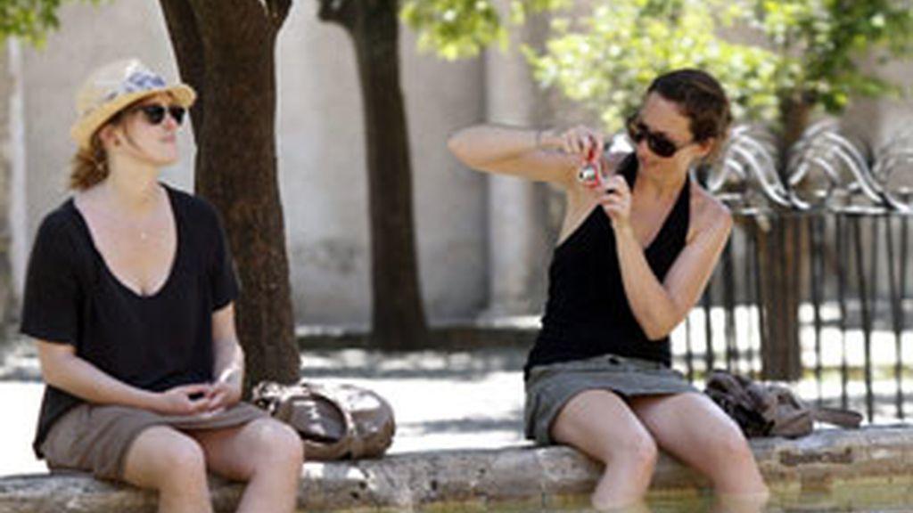 Dos turistas se refrescan en una de las fuentes del patio de Los Naranjos de la mezquita-catedral de Códoba. Foto: EFE