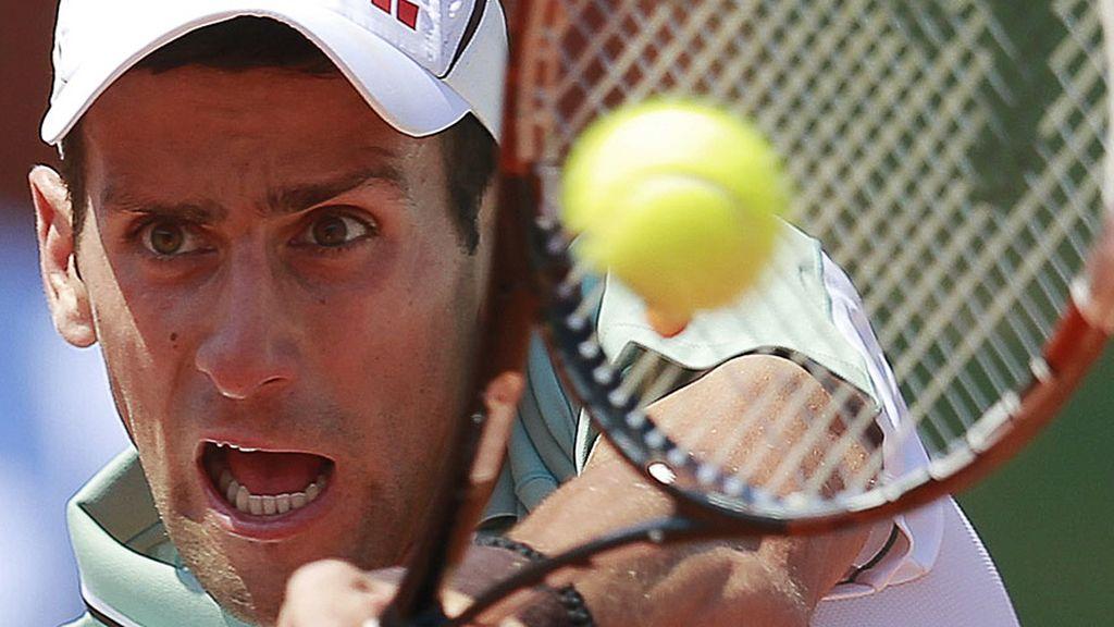 Djokovic, concentrado, devuelve una bola de revés a Nadal