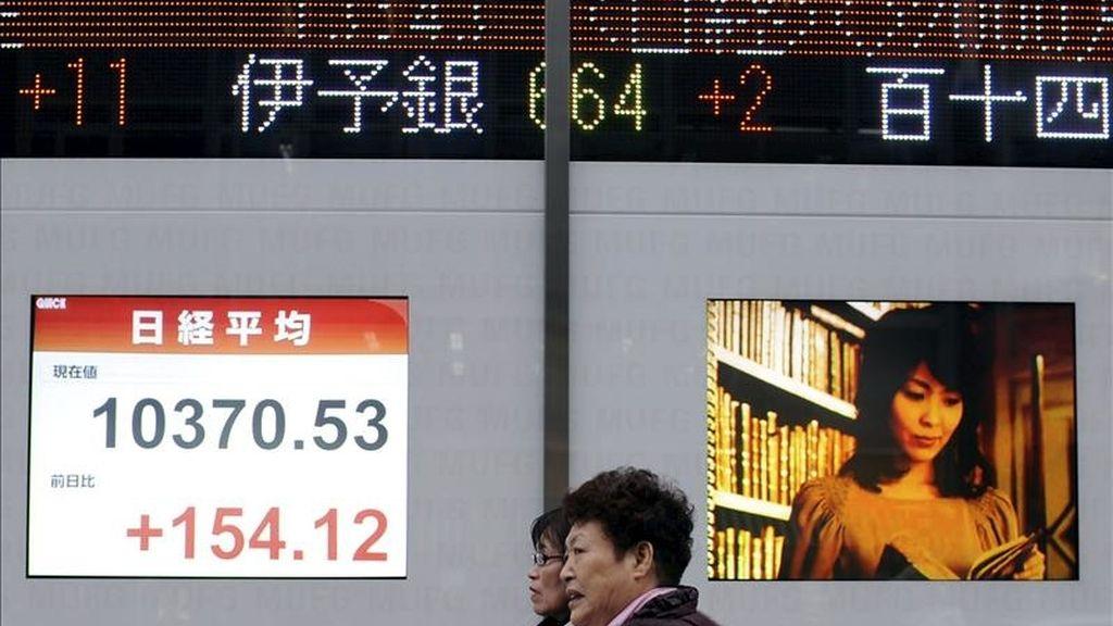 Dos mujeres caminan delante de una pantalla de la Bolsa de Tokio, Japón. EFE/Archivo