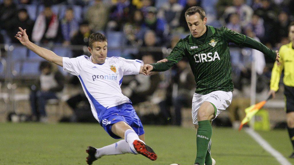 El betico Nacho se lleva el balón ante la entrada del delantero del Real Zaragoza Luis García