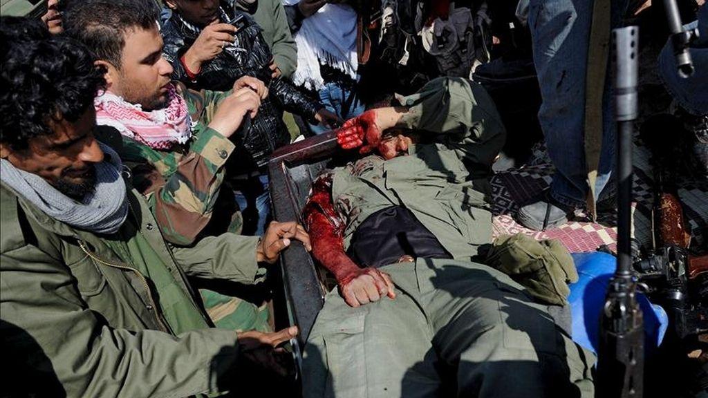 Soldados rebeldes libios toman fotografías de un soldado leal al líder libio Muamar el Gadafi que resultó herido, en la parte trasera de un vehículo, en la carretera entre Brega y Ajdabiya, en Libia. EFE