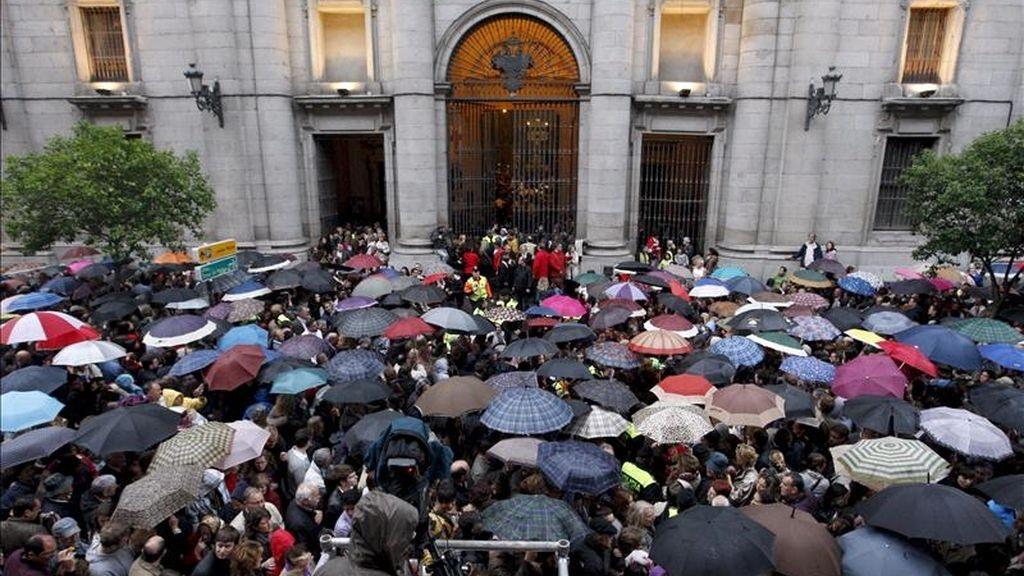 Miles de madrileños se agolpan junto a la fachada de la Real Colegiata de San Isidro, en Madrid, de donde debería partir la procesión de Nuestro Padre Jesús del Gran Poder y María Santísima de la Esperanza Macarena que ha sido suspendida por la lluvia que cae sobre Madrid en la tarde del Jueves Santo. EFE