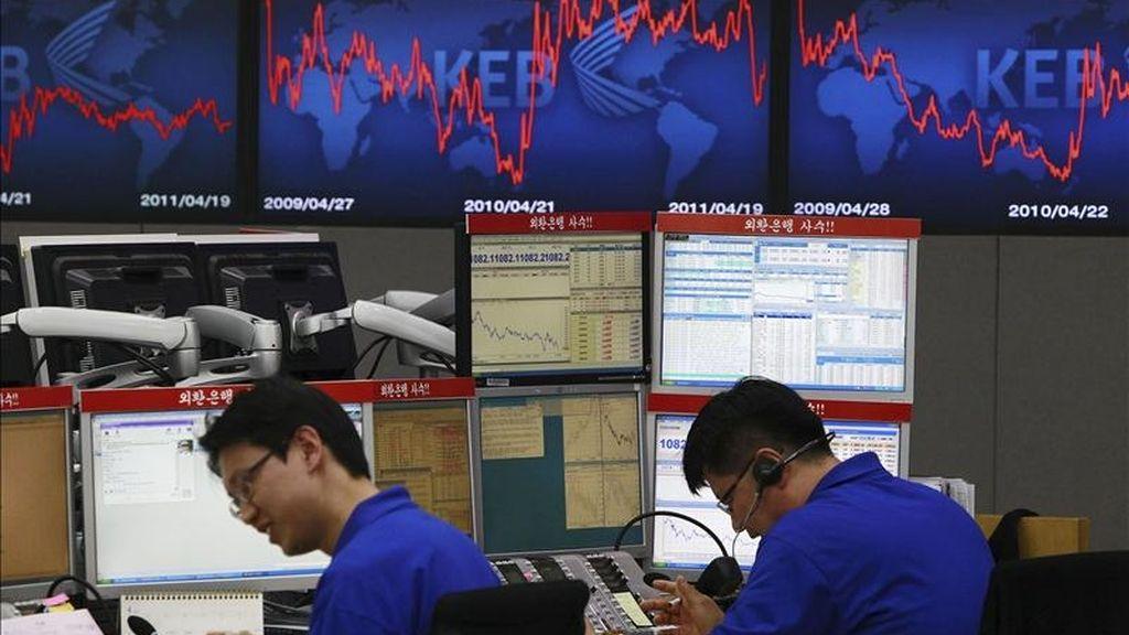 Un par de agentes de bolsa trabajan en el Banco de Cambio en Seúl (Corea del Sur). EFE/Archivo