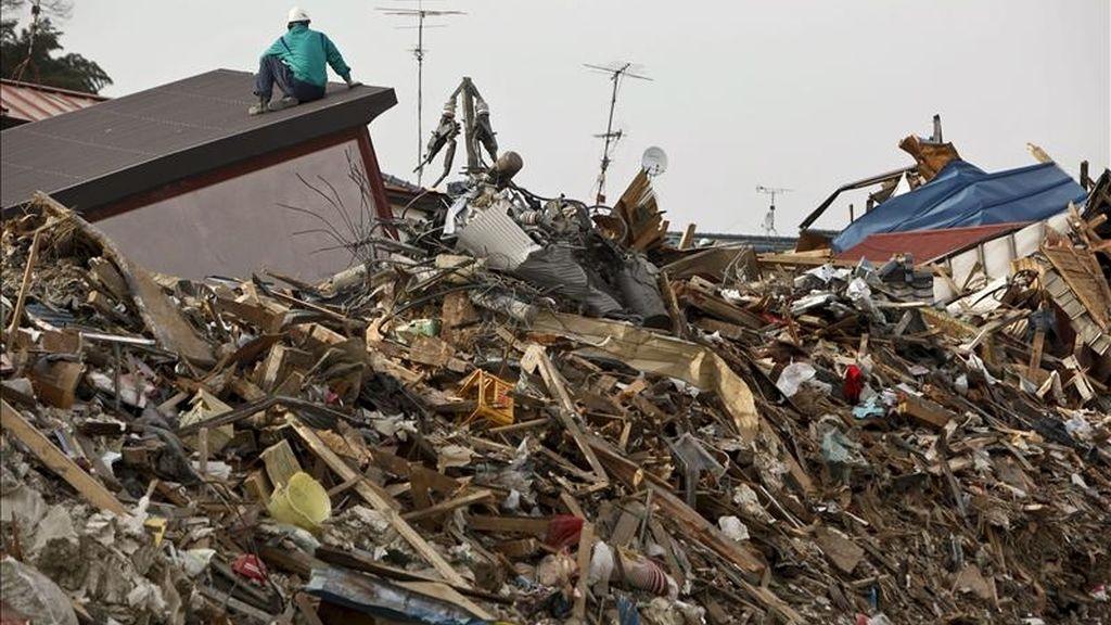 Un hombre se sube a una montaña de escombros en la devastada ciudad de Ishinomaki, en la prefectura de Miyagi (Japón). EFE