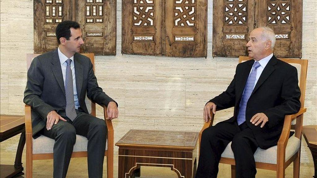 Fotografía facilitada por la agencia siria de noticias SANA que muestra al presidente sirio, Bachar al Asad, charlando con el nuevo gobernador en la provincia de Homs, Gasal Mustafa Abdelal, al que Asad nombró en su cargo. EFE