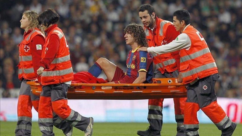 El defensa del FC Barcelona, Carles Puyol, es sacado del campo en camilla, durante el partido, correspondiente a la trigésimo segunda jornada de Liga en Primera División, que Real Madrid y FC Barcelona jugaron el pasado 16 de abril en el estadio Santiago Bernabéu, en Madrid. EFE/Archivo
