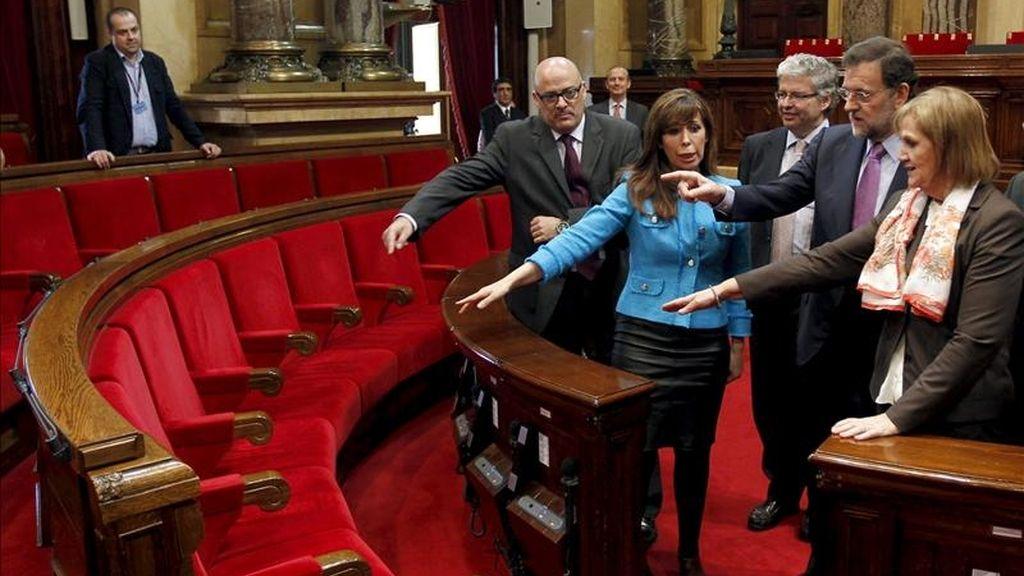 La presidenta del Parlament, Nuria de Gispert (d), y la del Partido Popular de Cataluña (PPC), Alicia Sánchez-Camacho, acompañados de los miembros de la mesa, Lluís Corominas (i), y Jordi Cornet (c), muestran al líder de los populares nacionales (PP), Mariano Rajoy (2ºd), el escaño del presidente de la Generalitat, durante la visita que ha realizado esta mañana a la cámara catalana. EFE