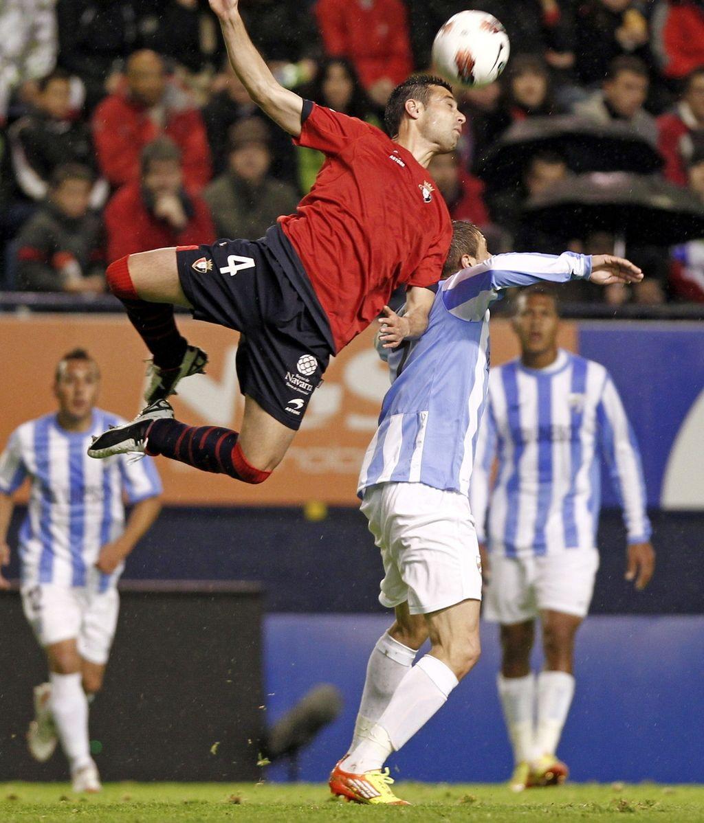 El defensa de Osasuna Miguel Flaño cabecea un balón ante el centrocampista del Málaga, Joaquín Sánchez