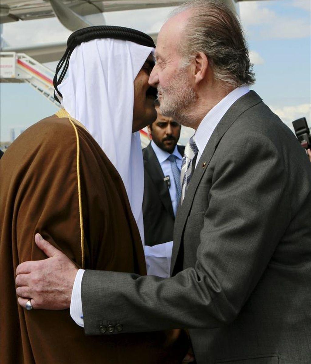 El rey don Juan Carlos saluda al emir de Catar, Hamad Bin Jalifa al-Thani, a la llegada de éste, acompañado de su esposa, Mozah Bint Nasser, al aeropuerto de Barajas, para una visita oficial en la que reforzarán las relaciones bilaterales entre ambos países. EFE