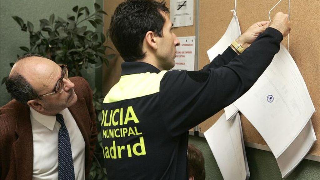Un agente de la Policía Municpal de Madrid cuelga los listados con el censo electoral en un colegio. EFE/Archivo