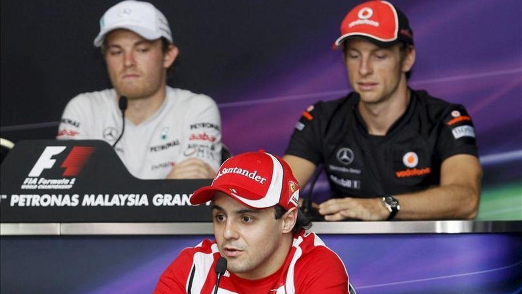 El piloto brasileño de Fórmula Uno de la escudería Ferrari, Felipe Massa (delante), el británico de McLaren Mercedes, Jenson Button (dcha), y el alemán de Mercedes GP, Nico Rosberg, atienden a los medios durante la rueda de prensa ofrecida en el circuito de Sepang. EFE