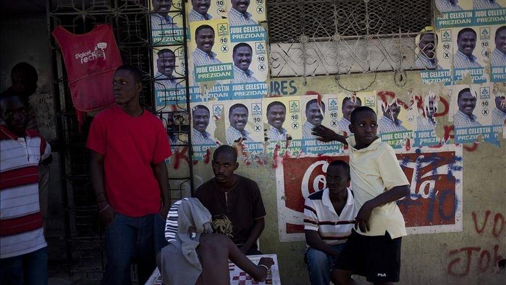 Varios jóvenes permanecen junto a carteles electorales del candidato presidencial del partido Inite, Jude Celestin, en Puerto Príncipe (Haití). EFE/Archivo