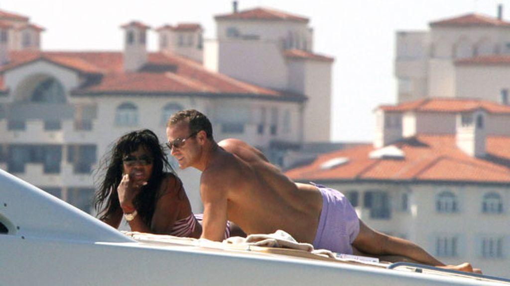 La modelo Naomi Campbell se tuesta al sol sobre la cubierta muy bien acompañada