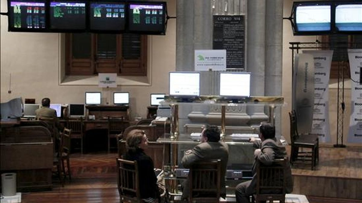 Tres inversores conversan mientras siguen las cotizaciones en la bolsa de Madrid, en la Plaza de la Lealtad. EFE/Archivo