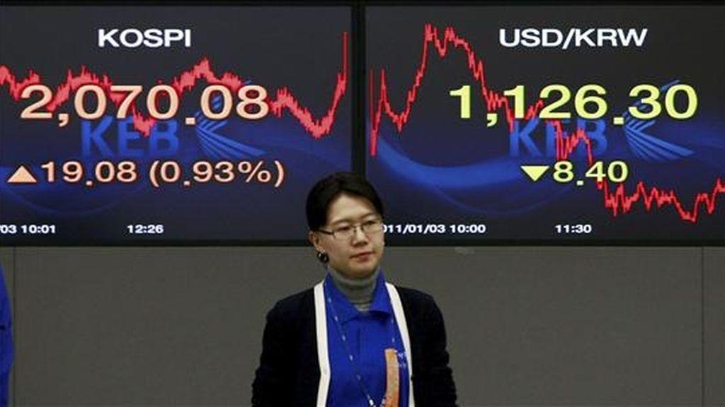 Una agente de volsa permanece junto a dos monitores en el Banco de Cambio de Seúl (Corea del Sur). EFE/Archivo